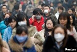 Cư dân đeo mặt nạ đi trong khói mù vào buổi sáng tại Bắc Kinh.