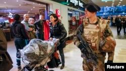 "Seorang tentara Perancis berpatroli di sebuah mall di Lyon (16/1) sebagai bagian dari siaga keamanan ""Vigipirate"" sesudah terjadinya serangan teroris minggu lalu."