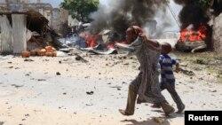 Dua orang anak Somalia lari menyelamatkan diri saat terjadinya ledakan di komplek pengadilan di Mogadishu, Minggu (14/4).