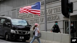 香港当地时间10月27日星期二,王同学和另外三人进入美国驻港澳总领馆寻求帮助。图为在美国驻港澳总领事馆外的一次抗议活动中一名抗议者举着一面美国国旗过马路。(美联社2020年7月4日资料照)