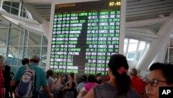 인도네시아 발리 국제공항 터미널에서 승객들이 화산 분화로 취소된 비행기 출도착 정보를 확인하고 있다.