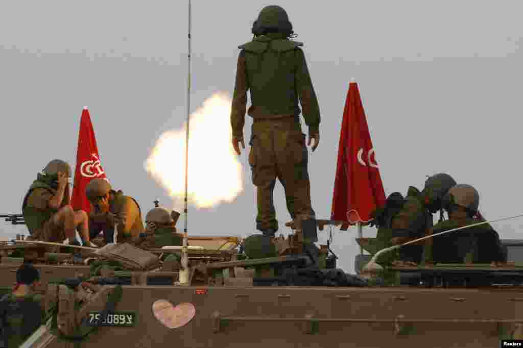 Israeli soldiers stand on an armored personnel carrier outside the central Gaza Strip as they fire mortar shell towards Gaza before a cease-fire, Aug. 1, 2014.