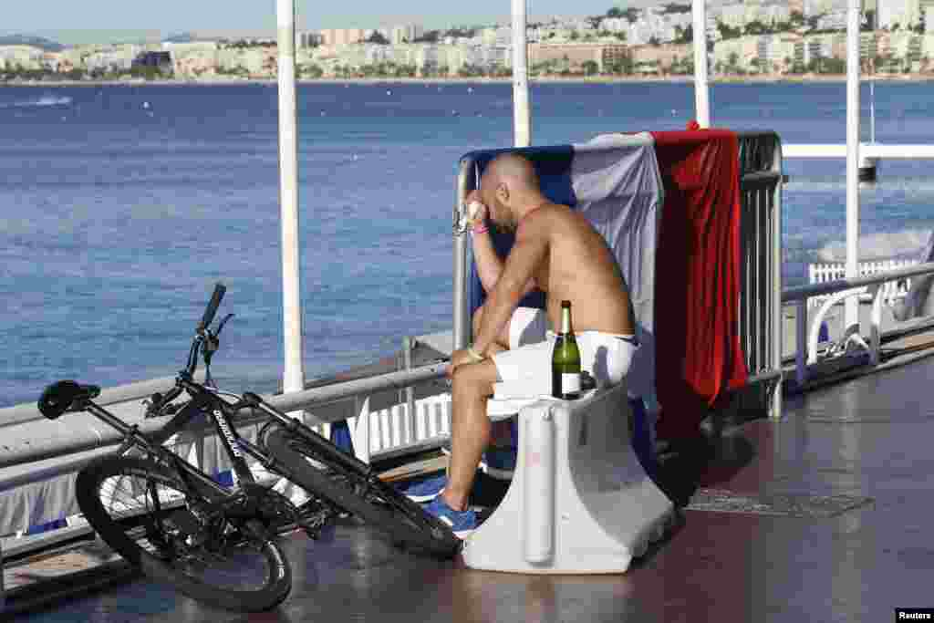 A man reacts as he sits near a French flag along the beachfront the day after a truck ran into a crowd at high speed killing scores celebrating the Bastille Day July 14 national holiday on the Promenade des Anglais in Nice, France, July 15, 2016.