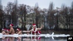 Para anggota kelompok Berlin Seals menggelar tradisi tahunan mereka merayakan Natal dengan terjun ke dalam sungai Oranke yang bekudi Berlin, Jerman, 25 Desember 2012. (AP Photo/Markus Schreiber)