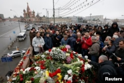 People gather at the site where Boris Nemtsov was recently murdered, with St. Basil's Cathedral seen in the background, in central Moscow, Feb. 28, 2015.
