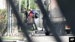 Rombongan warga Italia yang dievakuasi dari Wuhan, China menggunakan masker saat tiba di kompleks militer untuk menjalani karantina selama 14 hari di Roma, Senin, 3 Februari 2020. (Foto: AP)