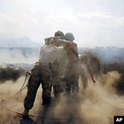"""U.S. soldiers from Task Force """"Cacti"""" are enveloped with smoke as they fire 120 mm mortar at Taliban positions from Combat Outpost Penich, in Khas Konar district in Kunar province, eastern Afghanistan, September 30, 2011"""
