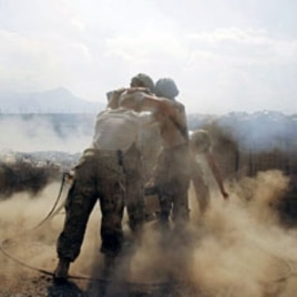 "U.S. soldiers from Task Force ""Cacti"" are enveloped with smoke as they fire 120 mm mortar at Taliban positions from Combat Outpost Penich, in Khas Konar district in Kunar province, eastern Afghanistan, September 30, 2011"