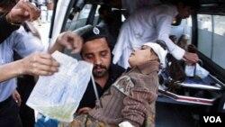 Seorang pria Pakistan mengangkut seorang anak perempuan yang terluka akibat bom bunuh diri, dari ambulans menuju sebuah rumah sakit di Peshawar, 5 Maret 2010.