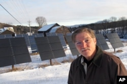Jeff Forward stands in front of solar panels, which are part of a community array, on his property in Richmond, Vt., Jan. 22, 2016. Vermont's commitment to renewable energy has created a job-producing boom in renewable energy projects.