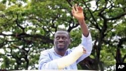 Uganda's Forum for Democratic Change leader Kizza Besigye waves to his supporters as he is blocked from driving to work in Kampala, prior to his arrest at gunpoint, April 28, 2011