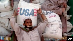 An Afghan refugee collects a bag of wheat being distributed by the World Food Program and USAID.