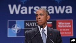 President Barack Obama pauses while speaking about the events in Dallas at the beginning of his news conference at PGE National Stadium in Warsaw, July 9, 2016.