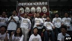 Những người tham gia biểu tình phản đối đứng dưới biểu ngữ trước khi tuyệt thực, 28/3/2014.