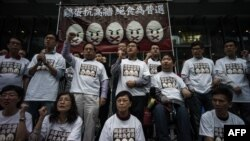 """Protesters stand under a banner as they prepare to go on a hunger strike to call for """"true"""" universal suffrage in Hong Kong, March 28, 2014."""