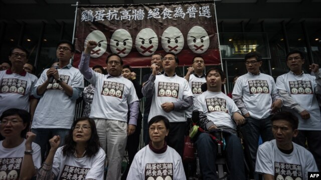 "Protesters stand under a banner as they prepare to go on a hunger strike to call for ""true"" universal suffrage in Hong Kong, March 28, 2014."
