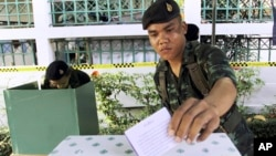 FILE - A Thai soldier casts his vote during the general election at a polling station in Bangkok, Thailand, Feb. 2, 2014. Thailand has taken another step toward holding elections in 2019 by easing some restrictions on political activities to allow parties to conduct basic functions, but they are still barred from campaigning.