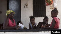 A grandmother gives her grandchildren school lessons on their porch in Sierra Leone's capital Freetown, April 24, 2012.