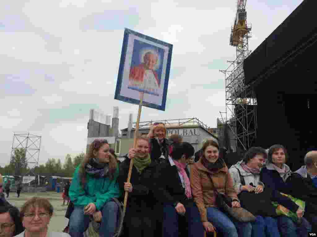 Sekelompok orang menunggu upacara yang disiarkan lewat televisi dari Vatikan di Crakow, Ukraina, 27 April 2014. (Jerome Socolovsky/VOA)