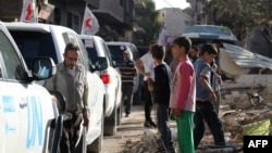 Vehicles of the International Committee of the Red Cross (ICRC), the Syrian Arab Red Crescent and the United Nations wait on a street after an aid convoy entered the rebel-held Syrian town of Daraya, southwest of the capital Damascus, on June 1, 2016.