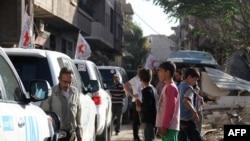 Kendaraan Komite Internasional untuk Palang Merah (ICRC), Bulan Sabit Merah Arab-Suriah dan PBB menunggu di jalanan setelah konvoi bantuan memasuki wilayah yang dikuasai oleh pemberontak di Daraya, Suriah (1/6).