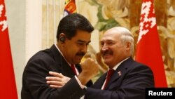Belarussian President Alexander Lukashenko (R) and his Venezuelan counterpart Nicolas Maduro embrace as they attend a joint news conference following their meeting at the Independence Palace in Minsk, Belarus October 5, 2017.