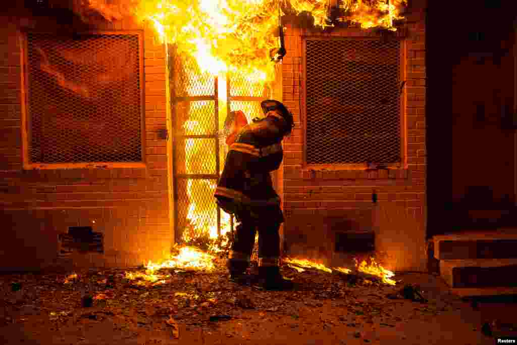 A firefighter uses a saw to open a metal gate while fighting a fire in the early morning hours Tuesday in Baltimore, Maryland   The city erupted in violence Monday after the funeral of Freddie Gray, a 25-year-old black man who died earlier this month in police custody.