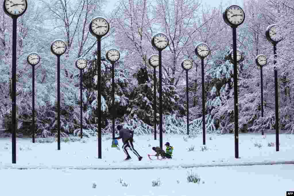 A man pulls children on a sledge through the snow-covered clock park by artist Klaus Rinke made of 24 station clocks, in Düsseldorf, western Germany.