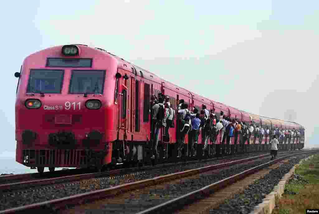스리랑카 콜롬보에서 승객들이 매달린채 기차를 타고 이동 중이다. 요금이 저렴하기 때문에 스리랑카에서 기차는 가장 인기있는 교통수단이다.