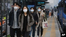 People wearing masks to protect from air pollution walk at a bus station in Seoul, South Korea, Wednesday, March 6, 2019. (AP Photo/Ahn Young-joon)