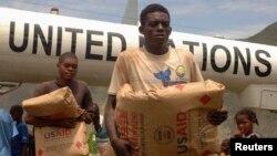 지난 2010년 지진이 강타한 아이티 주민들이 유엔 산하 세계식량기구 WFP가 지원하는 구호품을 내리고 있다. (자료사진)