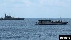 Kapal Angkatan Laut Australia (kiri) mengawasi sebuah kapal pencari suaka di dekat Pulau Christmas, Australia (foto: dok).