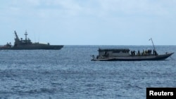 FILE - An Australian Navy boat (L) is positioned near a boat carrying 50 asylum seekers after it arrived at Flying Fish Cove on Christmas Island, about 1615 miles northwest of Perth, Aug. 7, 2011.