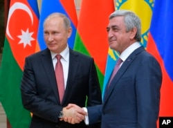 Russian President Vladimir Putin, left, and then-Armenian President Serzh Sargsyan shake hands ahead of an informal meeting of the CIS (Commonwealth of Independent States) leaders at the Novo-Ogaryovo residence outside in Moscow, Russia, Dec. 26, 2017.