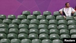 A spectator sits amid empty seats at the All England Lawn Tennis Club during a match at the London 2012 Olympics Games July 28, 2012.