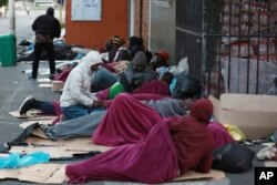 Refugees sleep on a sidewalk in Cape Town, South Africa, Friday, March 27, 2020, after South Africa went into a nationwide lockdown for 21 days in an effort to mitigate the spread to the coronavirus. (AP Photo/Nardus Engelbrecht)