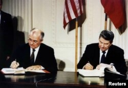 FILE - U.S. President Ronald Reagan (R) and Soviet President Mikhail Gorbachev sign the Intermediate-Range Nuclear Forces (INF) treaty in the White House, Dec. 8 1987.