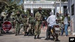Des soldats sénégalais fouillent un motocycliste à l'entrée du complexe de l'Etat à Banjul, Gambie, 24 janvier 2017.