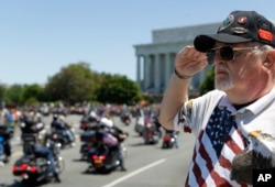 "FILE - Ken Caryl of Dale City, Virginia salutes the motorcyclists, many of them are veterans, as they ride across the Memorial Bridge into Washington during the annual Rolling Thunder ""Ride for Freedom,"" May 26, 2013."