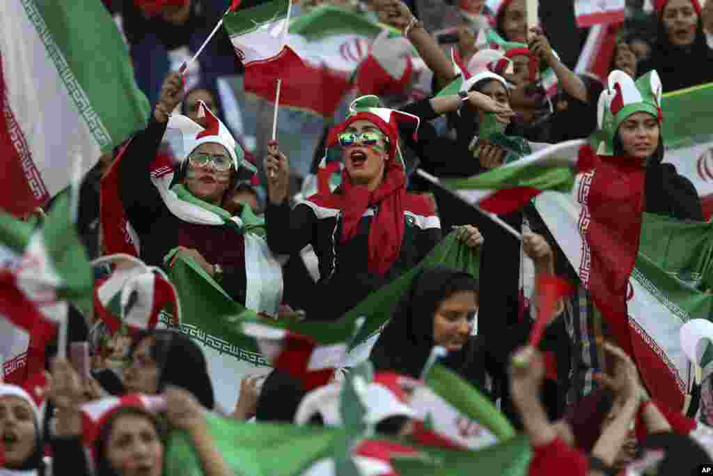 Iranian women cheer during a soccer match between their national team and Cambodia in the 2022 World Cup qualifier at the Azadi (Freedom) Stadium in Tehran. Iranian women were freely allowed into the stadium for the first time in decades.