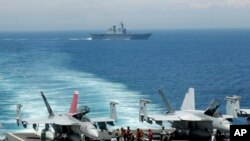Aviones caza de EE.UU. se preparan para despegar del portaaviones nuclear George Washington, mientras un barco de guerra surcoreano pasa cerca durante maniobras militares de los dos países en el Mar del Este frente a la costa surcoreana. Foto de archivo.