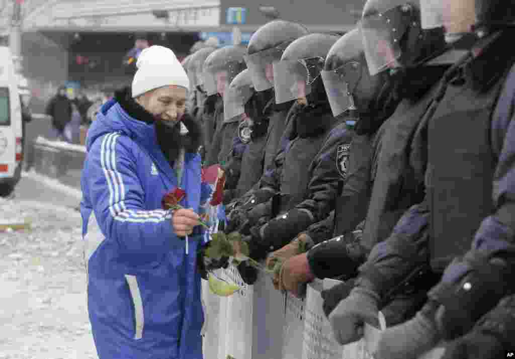 A pro-European Union activist gives flowers to riot police on a main street in central Kyiv, Dec. 10, 2013.