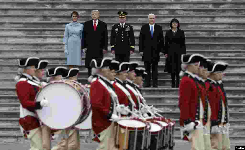 Newly inaugurated U.S. President Donald Trump (in red tie), first lady Melania (L), Vice President Mike Pence and his wife Karen (R) preside over a military parade during Trump's swearing ceremony in Washington, Jan. 20, 2017.