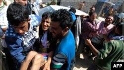 Người bị thương trong khi xô xát với cảnh sát, trong cuộc biểu tình đòi Tổng thống Yemen từ chức, được những người trong nhóm đưa đến bệnh xá dã chiến