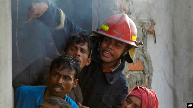 Bangladeshi firefighters and volunteers work to douse a fire at a two-storied garment factory in Dhaka, Bangladesh, January 26, 2013.