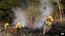 Bomberos tratan de abrir barreras contra el fuego en una colina en la zona de Oakmont, en Santa Rosa, California. Oct. 12, 2017.