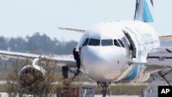 Un homme sort de l'avion détourné d'Egyptair depuis la fenêtre du cockpite à l'aéroport de Larnaca à Chypre le 29 mars 2016.