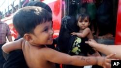 Trẻ em sắc tộc thiểu số Rohingya được đưa lên một chiếc xe buýt sau khi được giới chức chính phủ Thái Lan giải cứu khỏi các tay buôn người ở tỉnh Songkhla, miền nam Thái Lan, ngày 11/1/2013.