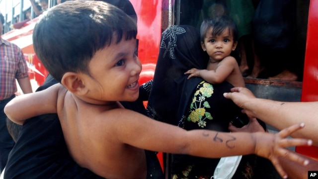 Rohingya minority children held by women board a bus after they were rescued by Thai authorities in Songkhla province, southern Thailand, Jan. 11, 2013.