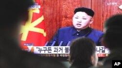 한국 서울역에서 1일 행인들이 김정은 북한 국방위 제1위원장의 신년사 관련 뉴스를 보고 있다.